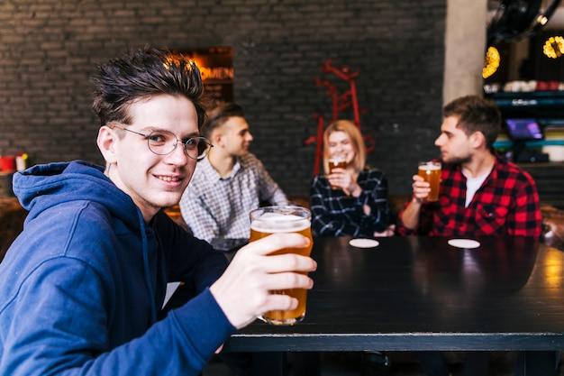 Retrato, de, um, homem, segurando, a, vidro cerveja, sentar-se, com, amigos Foto gratuita