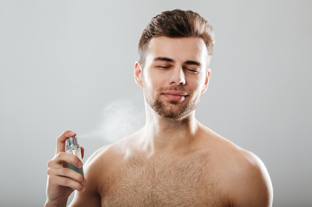 Retrato de um homem seminu bonito pulverizando perfume Foto gratuita