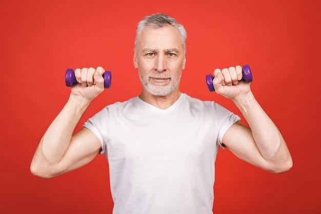 Retrato de um homem sênior exercitar com halteres. Foto Premium