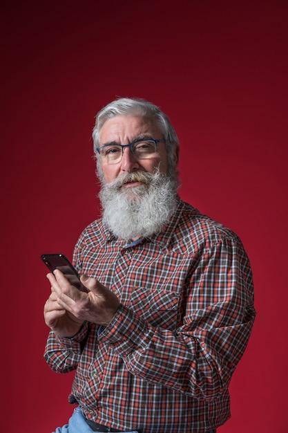 Retrato, de, um, homem sênior, óculos desgastando, segurando, esperto, telefone, em, mão, contra, vermelho, fundo Foto gratuita