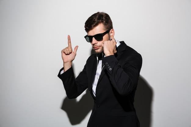 Retrato de um homem sério em fones de ouvido e óculos de sol Foto gratuita