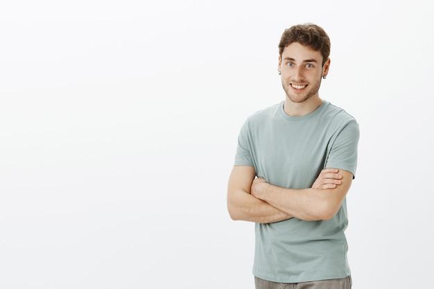 Retrato de um homem simpático e animado com cabelo loiro e brincos Foto gratuita
