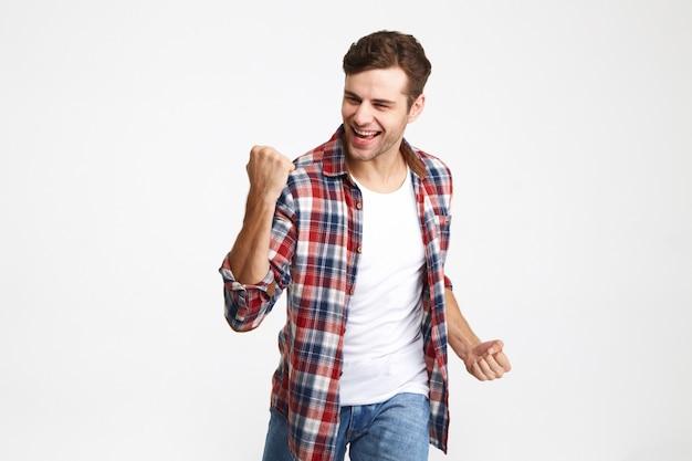 Retrato de um homem sorridente animado comemorando sucesso Foto gratuita