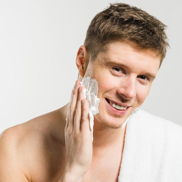 Retrato, de, um, homem sorridente, aplicando, espuma raspando, ligado, seu, rosto, com, mão, contra, branca, fundo Foto gratuita