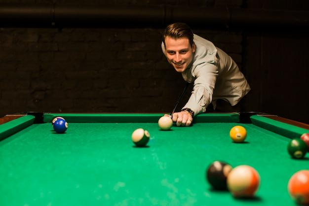 Retrato, de, um, homem sorridente, apontar, a, bola branca, enquanto, jogando snooker Foto gratuita