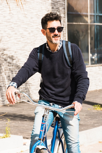 Retrato, de, um, homem sorridente, óculos sol, andar, ligado, seu, bicicleta Foto gratuita