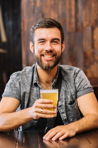 Retrato, de, um, homem sorridente, segurando, copo cerveja Foto gratuita