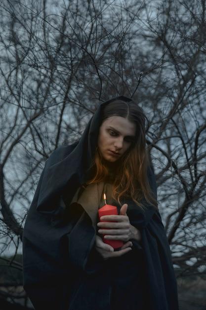 Retrato de um homem vestindo preto e segurando velas vermelhas Foto gratuita