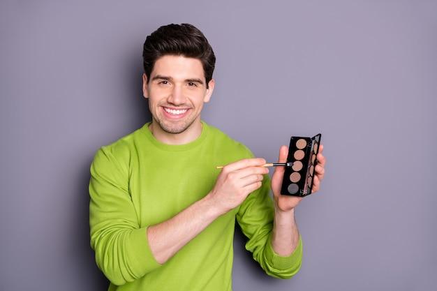 Retrato de um homem visagista positivo e confiante segurando paleta com pincel. o verdadeiro especialista pode fazer o rosto para festa à noite aniversário usar um macacão verde isolado sobre a parede de cor cinza Foto Premium