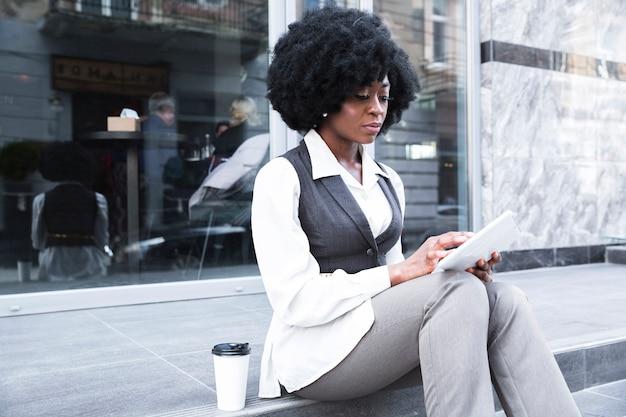 Retrato, de, um, jovem, africano, executiva, sentando, exterior, escritório, usando, tablete digital Foto gratuita