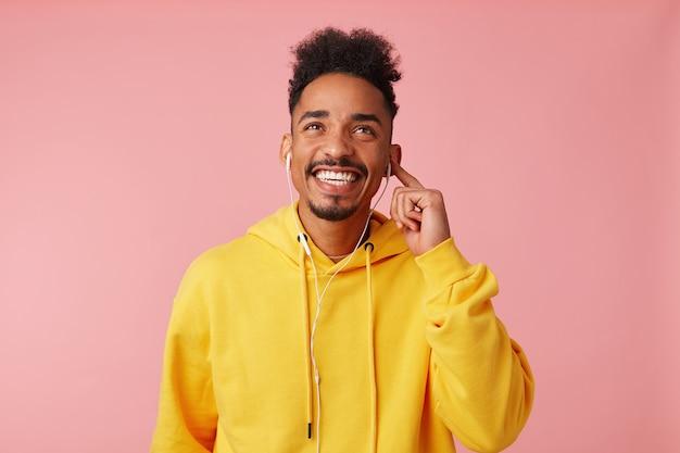 Retrato de um jovem afro-americano feliz com um capuz amarelo, desfrutando de sua música legal favorita em fones de ouvido, sonhadoramente olhando para cima, em pé e sorrindo amplamente. Foto gratuita