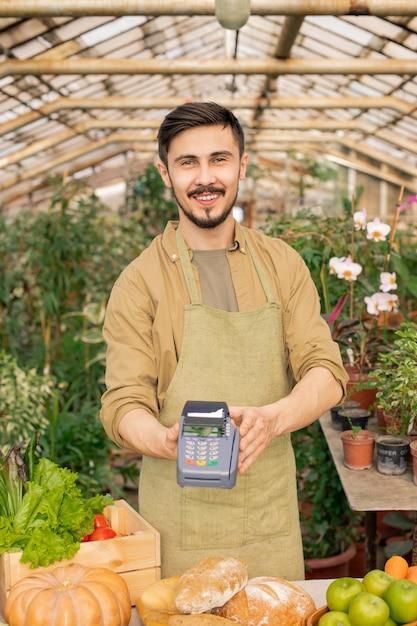 Retrato de um jovem agricultor positivo com barba segurando o terminal de pagamento acima do balcão de alimentos em um supermercado Foto Premium