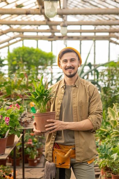 Retrato de um jovem alegre homem de efeito estufa com barba e bigode segurando um vaso de planta em uma estufa Foto Premium
