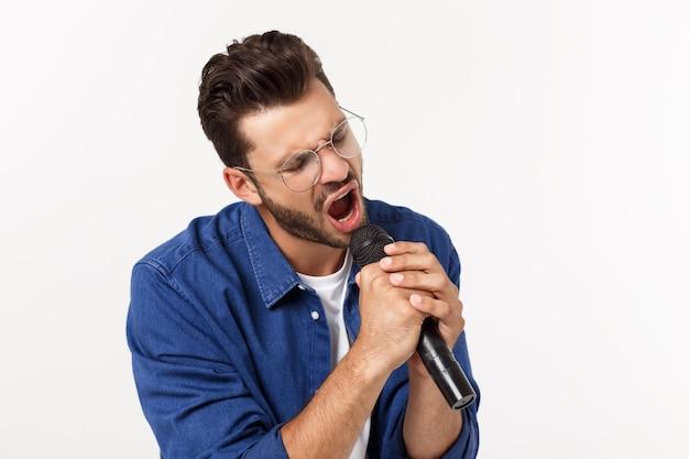 Retrato de um jovem animado em t-shirt isolado sobre fundo cinza, cantando. Foto Premium