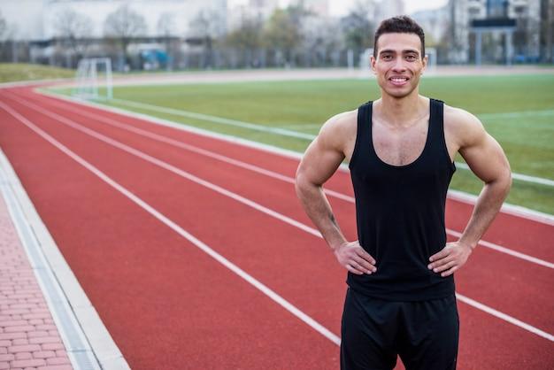 Retrato de um jovem atleta masculino sorridente em pé na pista de corrida Foto gratuita