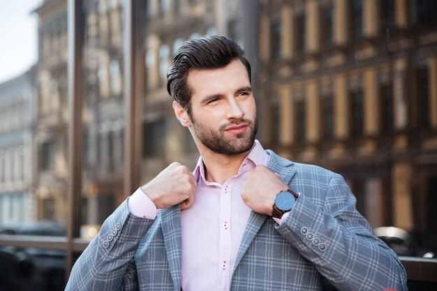 Retrato de um jovem atraente, endireitando sua jaqueta Foto gratuita