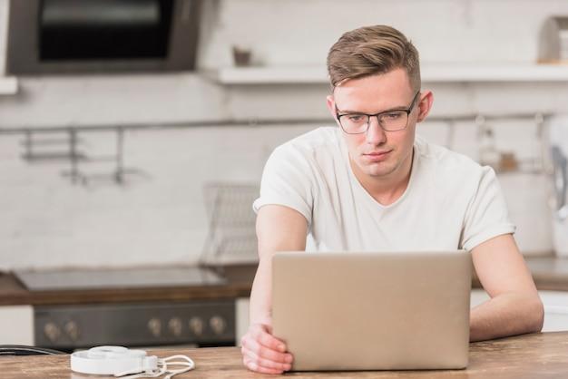 Retrato, de, um, jovem, bonito, homem olha, em, laptop Foto gratuita