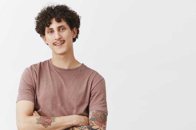 Retrato de um jovem bonito satisfeito e encantado com tatuagens de bigode e penteado encaracolado, sorrindo com sentimentos de felicidade e satisfação Foto gratuita