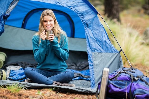 Retrato de um jovem caminhante bonito sentado em uma tenda Foto Premium