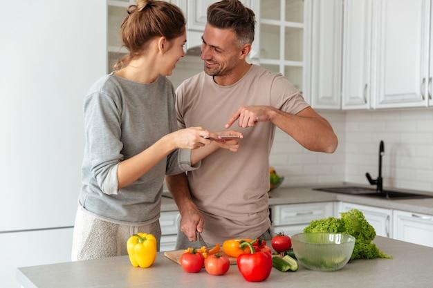Retrato de um jovem casal apaixonado, cozinhar salada juntos Foto gratuita