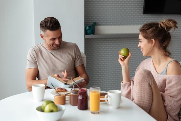 Retrato de um jovem casal apaixonado tomando café da manhã Foto gratuita