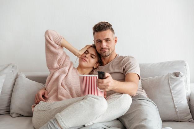 Retrato de um jovem casal atraente, comendo pipoca Foto gratuita