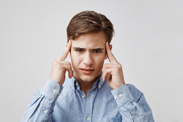 Retrato de um jovem com uma dor de cabeça terrível. Foto gratuita