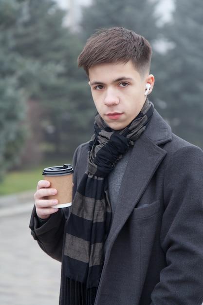 Retrato de um jovem com uma xícara de café, clima de inverno nevoento. foto em tons de cinza Foto Premium