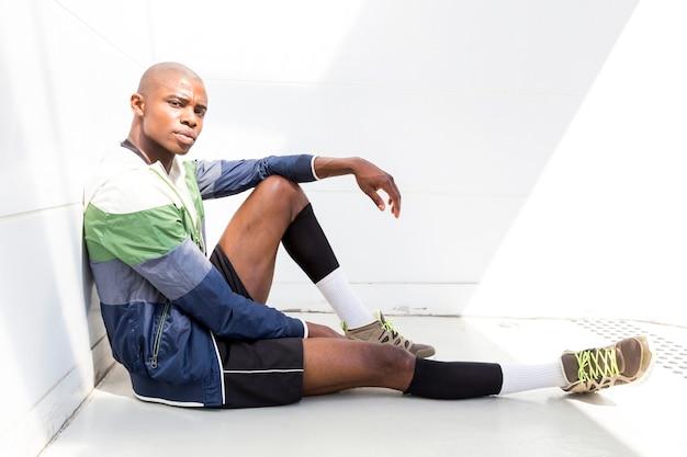 Retrato, de, um, jovem, corredor masculino, sentando, ligado, chão, contra, parede branca, olhando câmera Foto gratuita