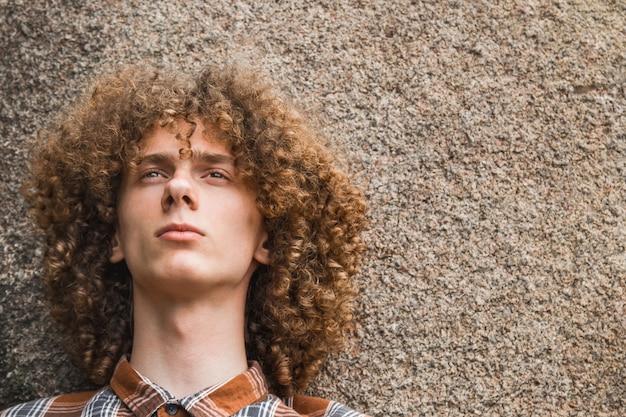 Retrato de um jovem de cabelos cacheados entre as pedras Foto Premium