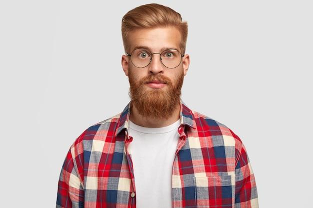 Retrato de um jovem designer de sucesso com uma espessa barba ruiva, parece surpreendentemente Foto gratuita