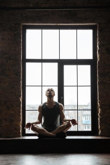 Retrato de um jovem desportista concentrado meditando Foto gratuita