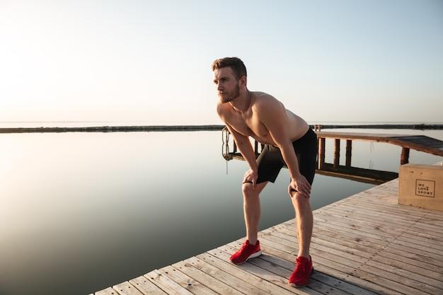 Retrato de um jovem desportista saudável descansando depois de correr ao ar livre Foto gratuita
