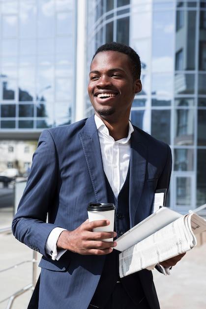 Retrato de um jovem empresário africano bem sucedido, segurando o copo de café descartável; jornal e tablet digital Foto gratuita