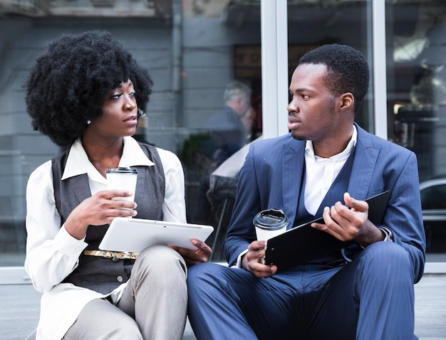 Retrato de um jovem empresário africano e empresária sentados juntos fora do escritório Foto gratuita