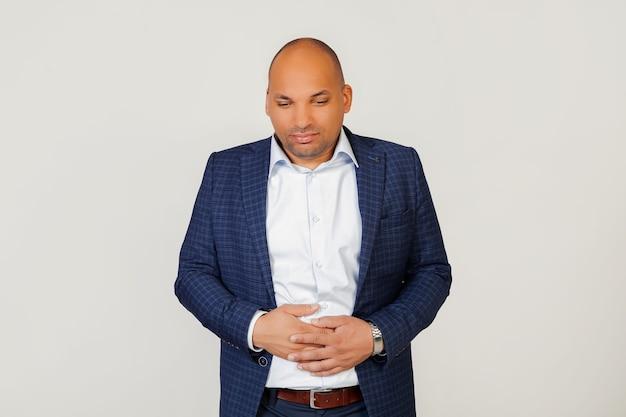 Retrato de um jovem empresário afro-americano doente, com uma mão na barriga devido a uma indigestão, passando mal. conceito de dor. Foto Premium