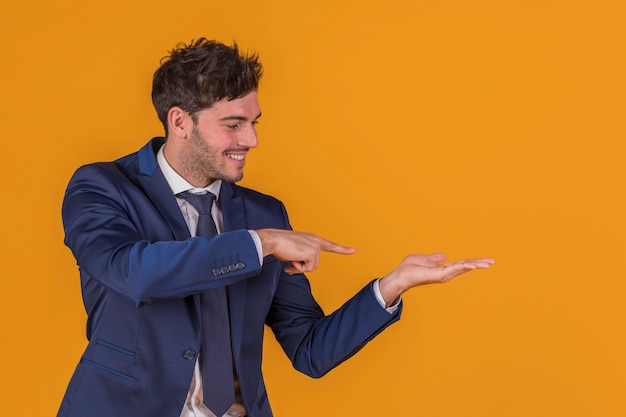Retrato de um jovem empresário apontando o dedo para algo contra um fundo laranja Foto gratuita