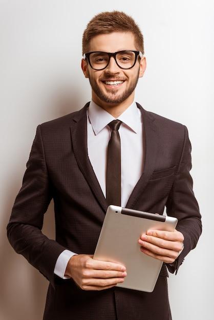 Retrato de um jovem empresário de sucesso está usando o tablet. Foto Premium