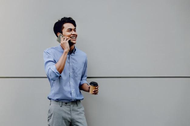 Retrato de um jovem empresário feliz usando telefone celular. estilo de vida das pessoas modernas. de pé junto à parede com uma xícara de café Foto Premium