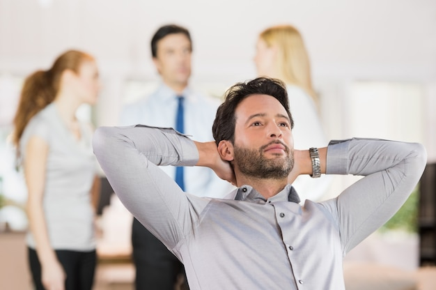 Retrato de um jovem empresário relaxante com as mãos atrás da cabeça no escritório. Foto Premium