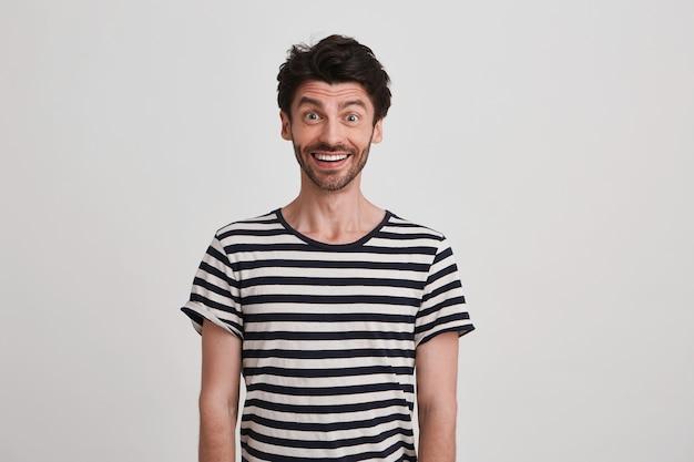 Retrato de um jovem espantado e alegre com cerdas e vestindo uma camiseta listrada se sente animado, de pé e parece feliz isolado sobre uma parede branca Foto gratuita