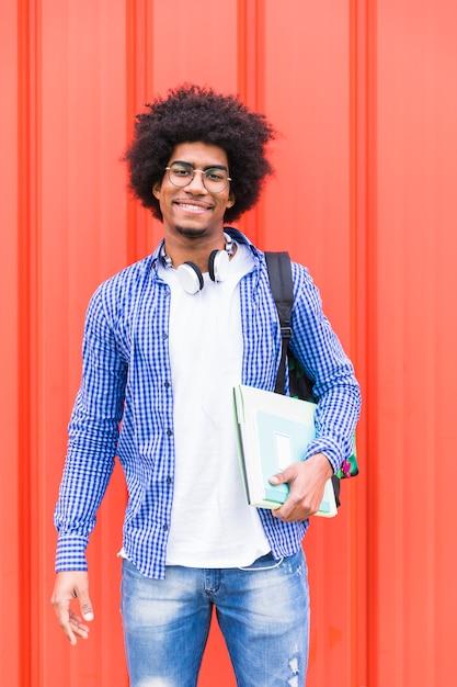 Retrato, de, um, jovem, estudante masculino, saco levando, ligado, ombro, e, livros, em, mão, ficar, contra, parede vermelha Foto gratuita