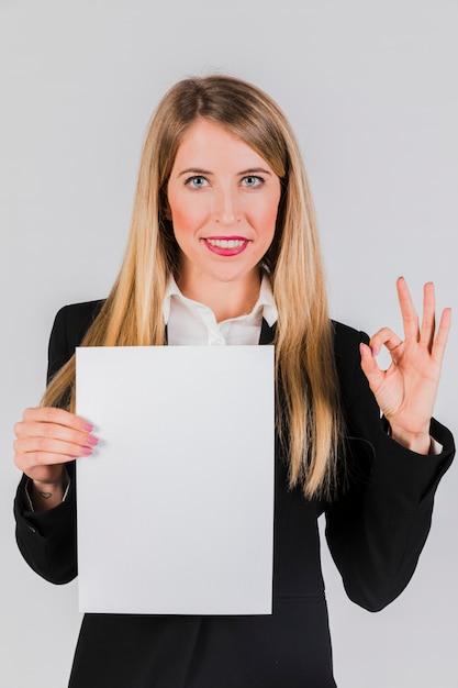 Retrato, de, um, jovem, executiva, segurando, a, papel branco, em, mão, mostrando, tá bom sinal Foto gratuita