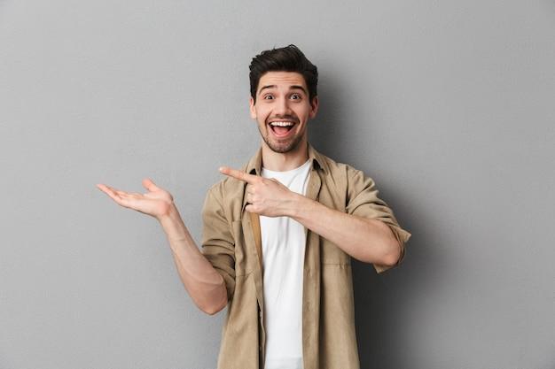 Retrato de um jovem feliz, apontando para o espaço da cópia Foto Premium
