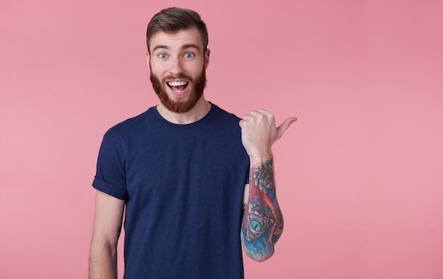 Retrato de um jovem feliz de barba vermelha, com a boca escancarada de surpresa, vestindo uma camiseta azul, apontando o dedo para copiar o espaço no lado direito isolado sobre o fundo rosa. Foto gratuita