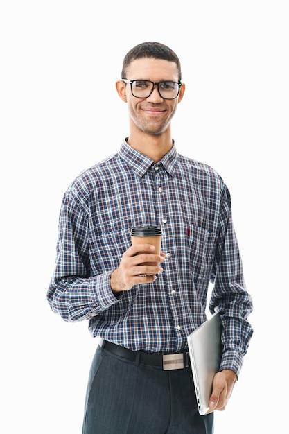 Retrato de um jovem feliz, vestindo uma camisa xadrez em pé sobre o branco, segurando a xícara de café e o computador laptop Foto Premium