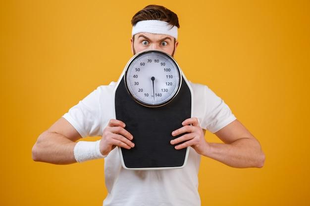 Retrato de um jovem fitness se escondendo atrás de balanças Foto gratuita