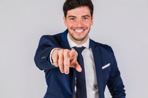 Retrato, de, um, jovem, homem negócios, apontar, seu, dedo, direção, câmera, contra, cinzento, fundo Foto gratuita