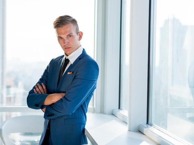 Retrato, de, um, jovem, homem negócios, com, braços dobrados Foto gratuita