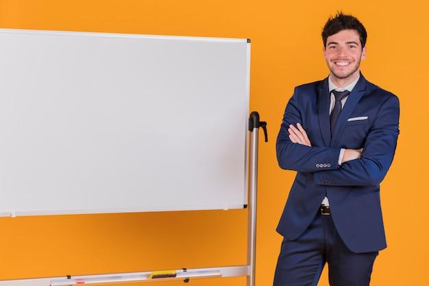 Retrato, de, um, jovem, homem negócios, com, seu, braço cruzou, ficar, perto, a, whiteboard, contra, um, laranja, fundo Foto gratuita